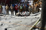 Pakistan's army and rescuers search for survivors in the wreckage of the collapsed building at the bomb site.