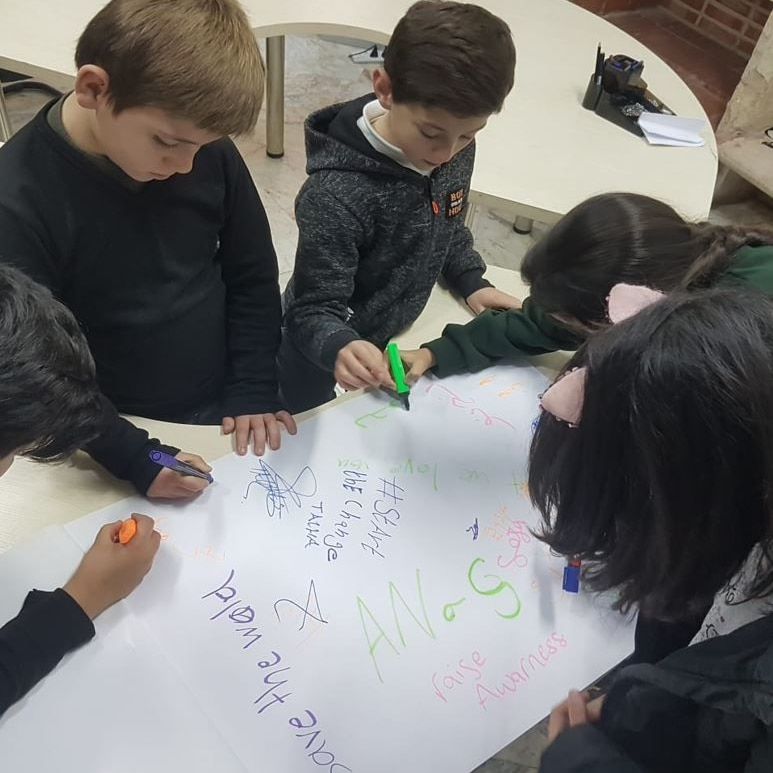 A group of children pictures writing messages on their drawings.