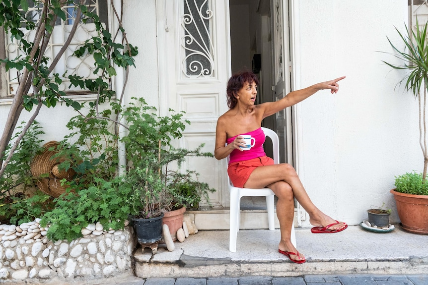 A woman in red shorts and a pink tube top sits on a chair outside her apartment drinking coffee