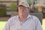 An elderly gentleman in a cap and glasses sits facing the camera, looking off to the side.