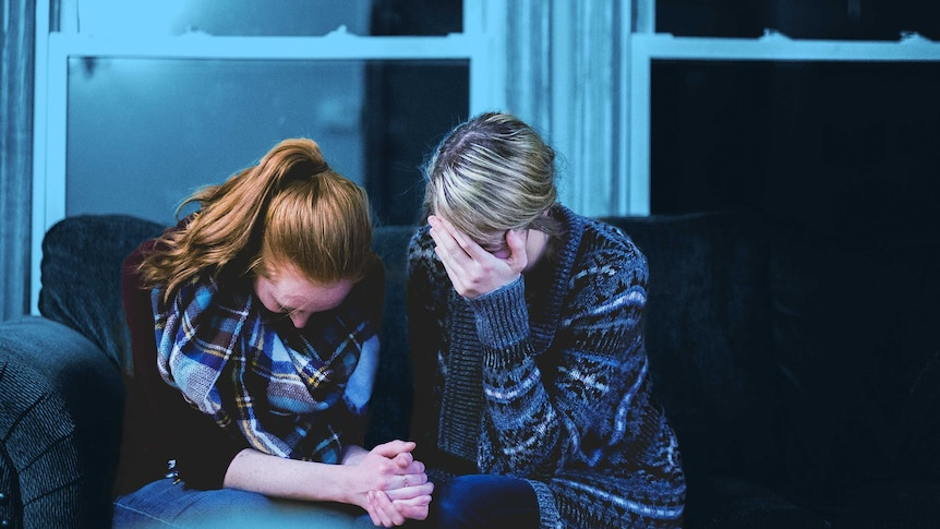Two women sit on a couch, holding hands, both of their heads bowed in grief supporting each other a sitting with the grief.