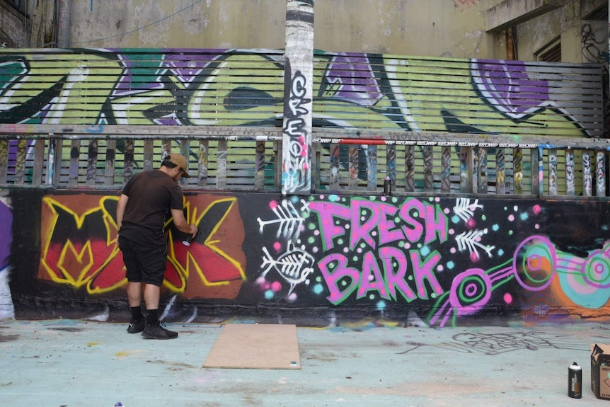 A man spray painting an industrial-looking wall with the words 'Fresh Bark' painted on it.