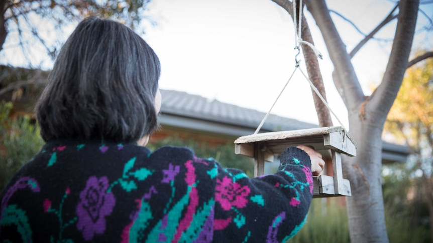 A woman with dark hair in a colourful jumper in a garden with a bird feeder. She is facing away from the camera.