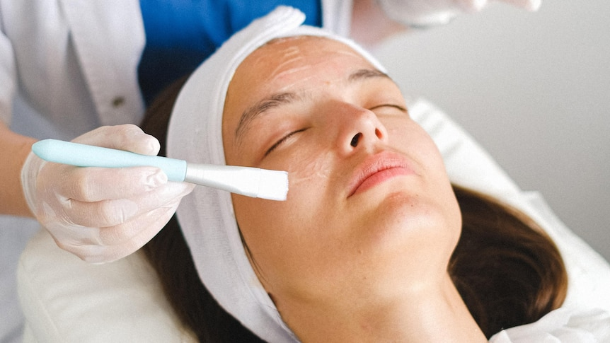 a woman lies on a salon bed as gel is applied to her face