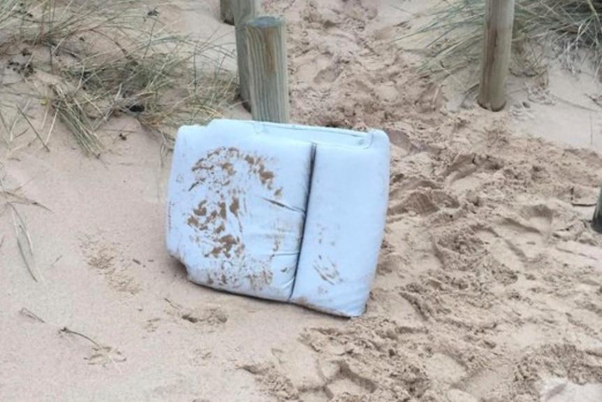A plane cushion sits on a beach, against a wooden stump