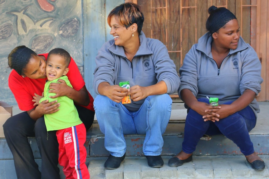 Three women and a young boy sitting on a step.