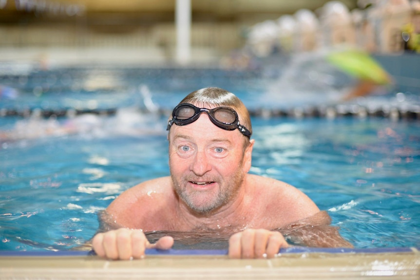 Amputee swimmer Michael Powell holds onto edge of a swimming pool with goggles on in Brisbane in July 2017