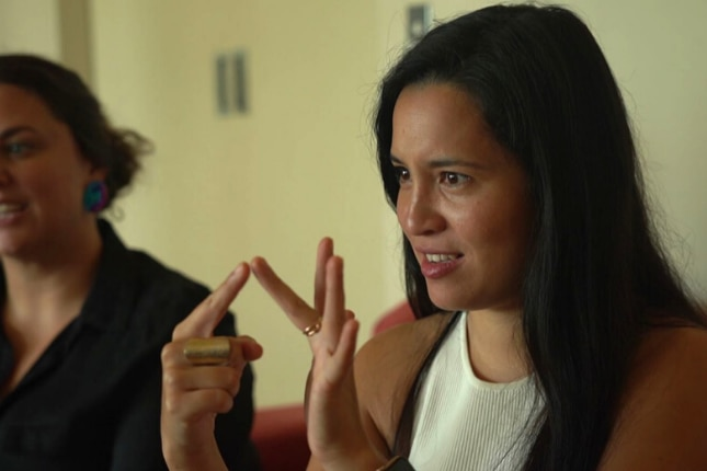 A young woman spells out a letter using Australian sign language