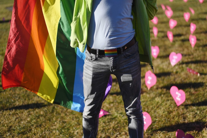 A man stands holding a rainbow flag in front of pink paper hearts decorating a grassy space.