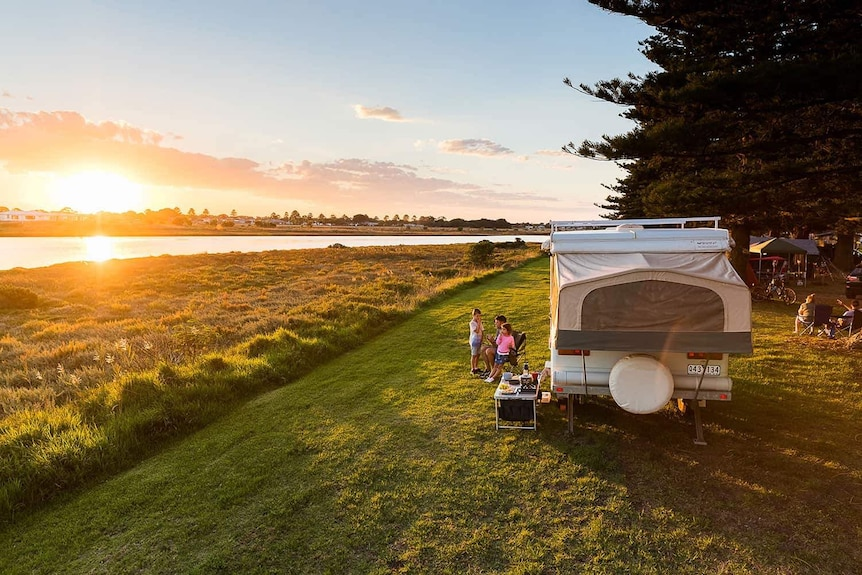 A family sits near their caravan, watching the sun set over a river.