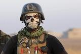 Soldier wears a skull mask.