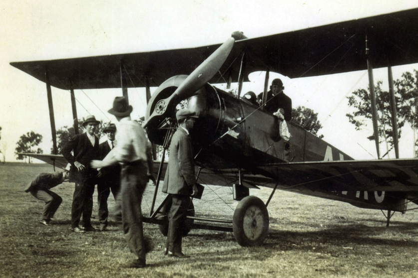 Black and white photo taken in the 1920s of a bi plane in a field with a passenger holding a white mail bag.