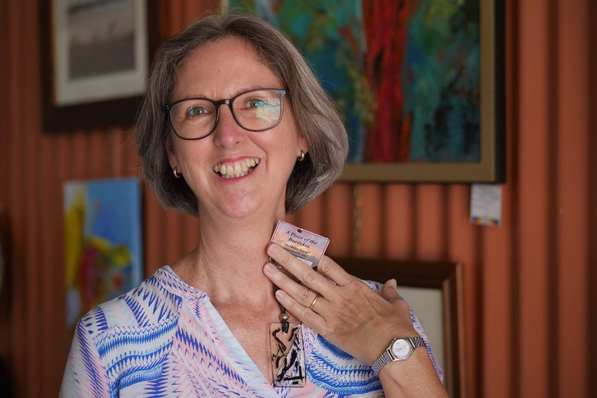 A smiling woman wearing glasses holds up to her neck a pendant made from clear resin and cane ash