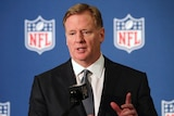 An NFL executive stands in front of a microphone speaking at a press conference.