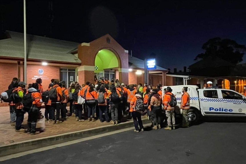 A group of people standing outside a police station