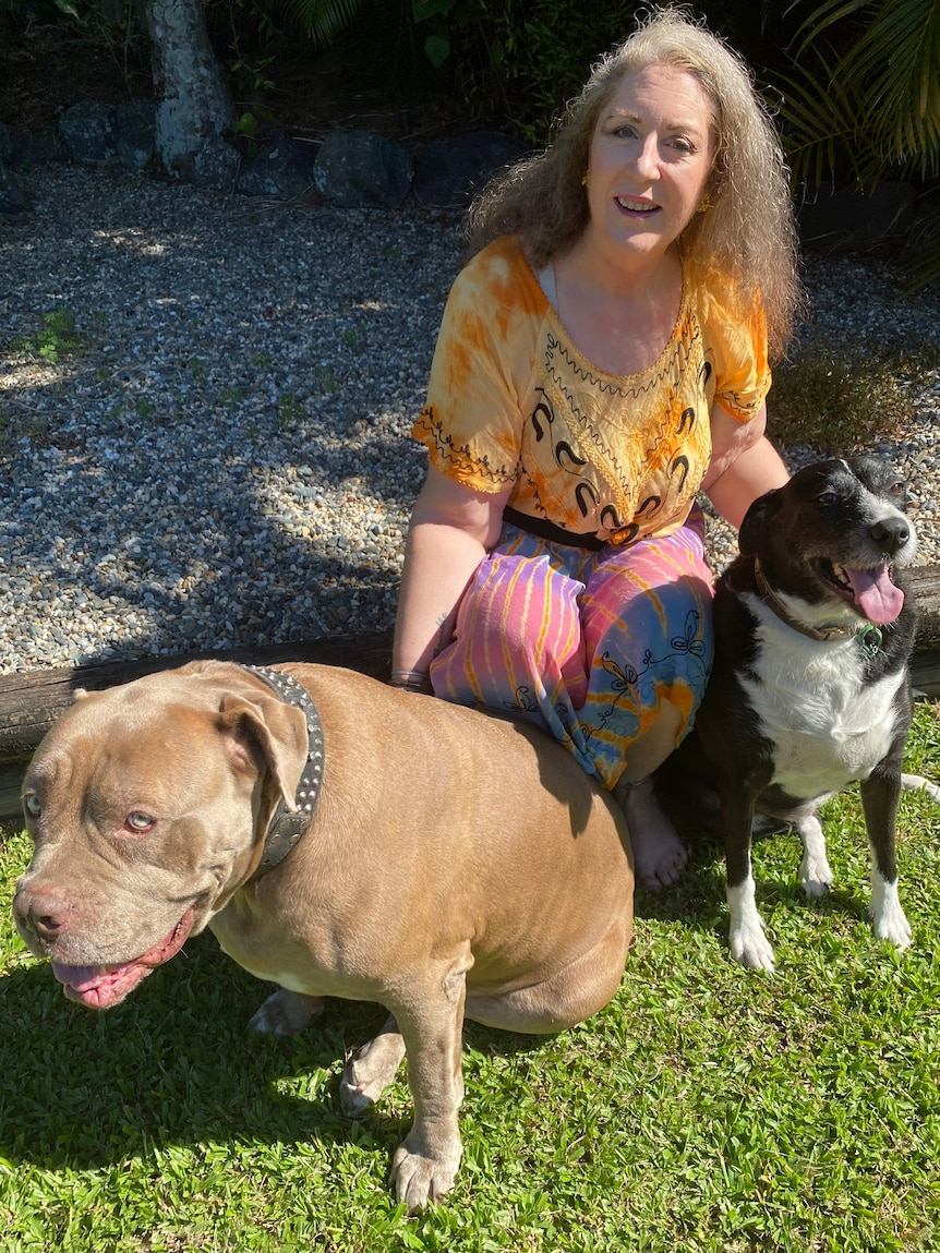 Marcella is kneeling down and patting two large dogs that look very happy.