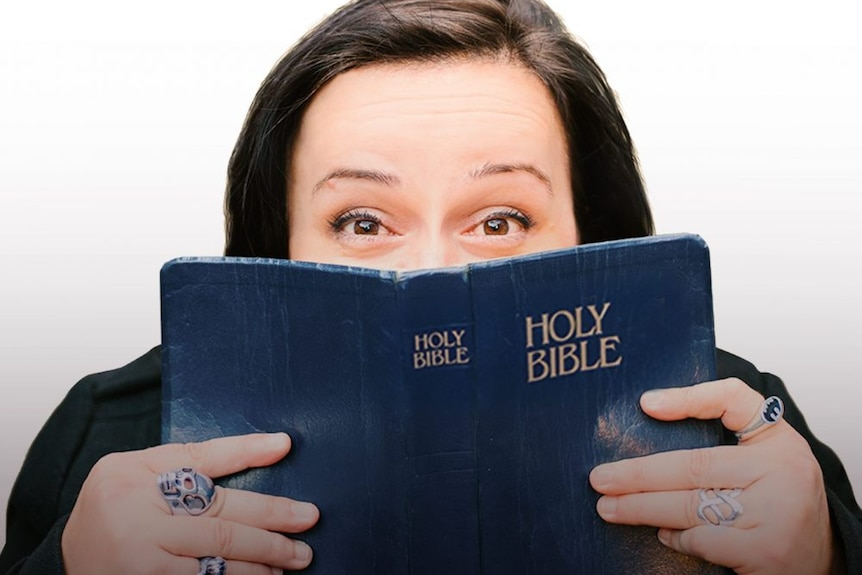A woman holds up a bible over her face