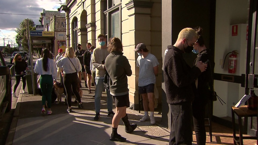 People line up for takeaway drinks outside a pub on a sunny day.