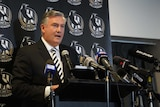 Eddie McGuire standing at a lectern in front of a banner with magpies logo.