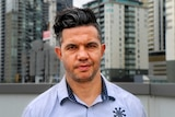 Joe Williams, with black hair and wearing a blue shirt, stands in front of a city background.
