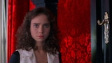 A still from the film Suspiria, with actress Jessica Harper with a concerned expression in front of a vivid red wall.