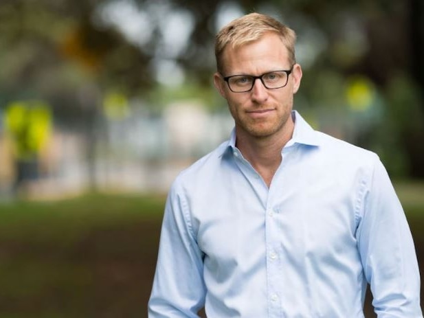 A slim, blond, bespectacled man standing in a leafy area.