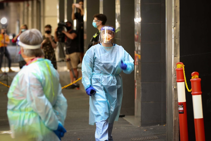 A woman wearing personal protective equipment including a gown, face shield, mask and gloves.