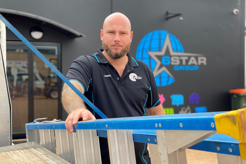 General Manager of electrical business 6 Star Group James Corea leaning on a ladder outside his business in Karratha.