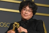Bong Joon Ho makes his two Oscar statues kiss at the Academy Awards ceremony.