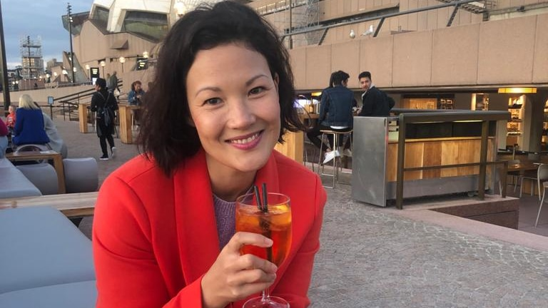 Comedian and writer Lizzy Hoo sitting outside Sydney Opera House with a cocktail.