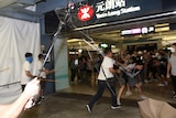 Viewing from within the scrum of a fight, you view three men in white shirts carrying poles and bamboo sticks attacking people.
