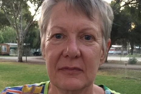 A woman in a caravan park stares unsmiling at the camera