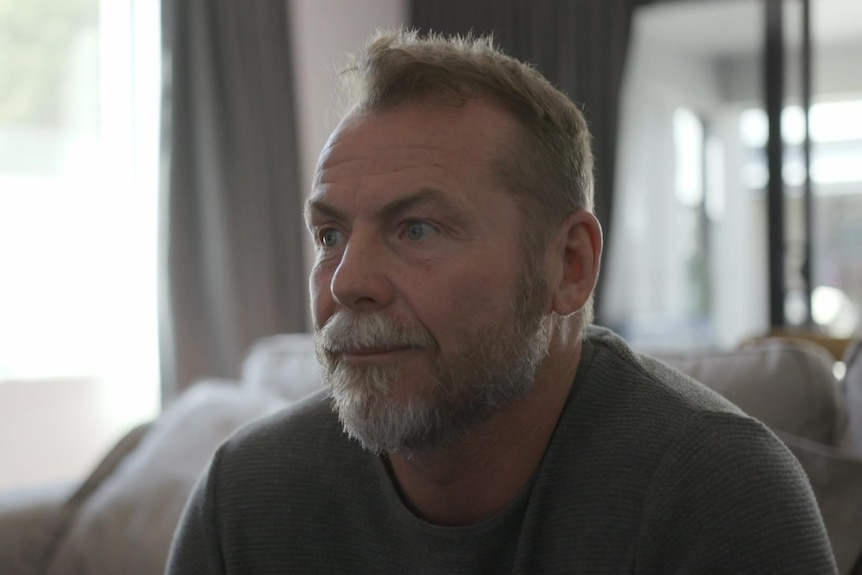 A middle-aged man with a beard sits on a sofa, looking off into the distance