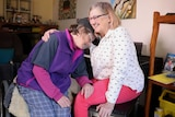 A middle-aged woman with hydrocephalus hugs her mother in their living room.