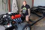 Will Barabas, a tall, stocky man with tattoos and a beard, sits in a black chassis with a red engine, inside a shed.