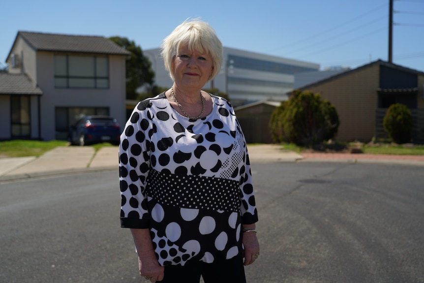 A woman with short blonde hair wearing a black and white top and necklace stands in a residential street