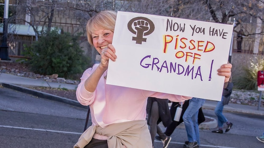 An smiling elderly woman with a bum bag holds up a sign that reads Now You've Pissed Off Grandma