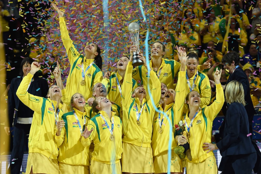 The Diamonds hold up the Netball World Cup trophy as confetti falls.
