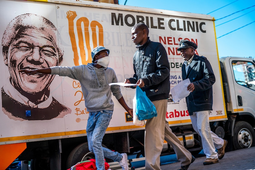 """Someone points the two men at something outside the frame.In the background, there is a truck sign that says """"Mobile clinic"""".."""
