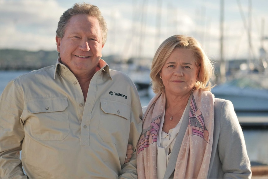 A man and a woman standing next to each other with boats in the background