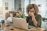A young woman suffering from stress holds her head while using a computer at her work desk.