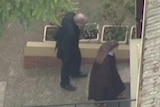 Aerial news footage shows Cardinal Pell being ushered inside the a church property in Melbourne by a nun.