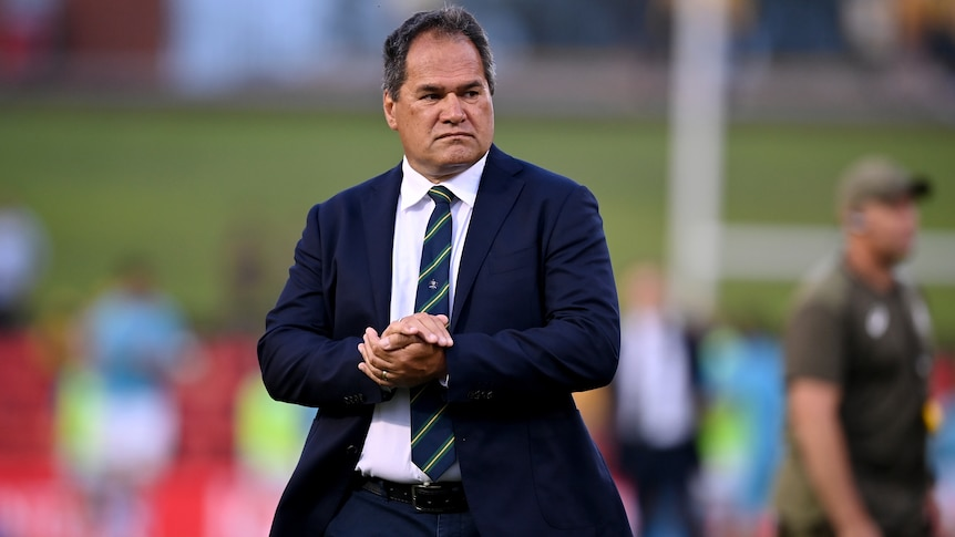 A serious looking rugby union coach clasps his hands together as he stands on the pitch after an international match.