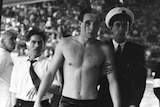 A photo of Hungarian water polo player Ervin Zádor being led away from a swimming pool by officials.