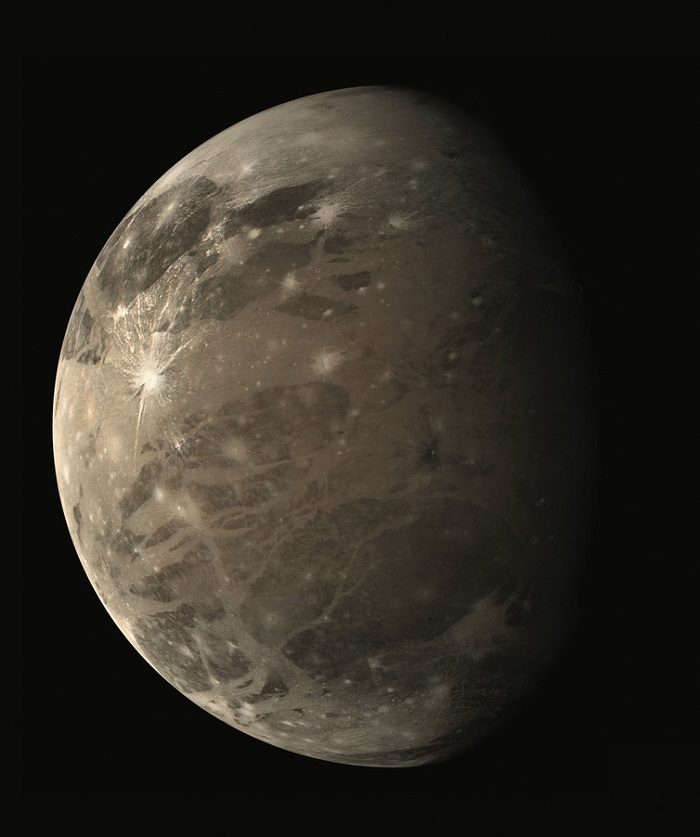 A view of Ganymede, grey-brown in colour and pocked with scars/craters