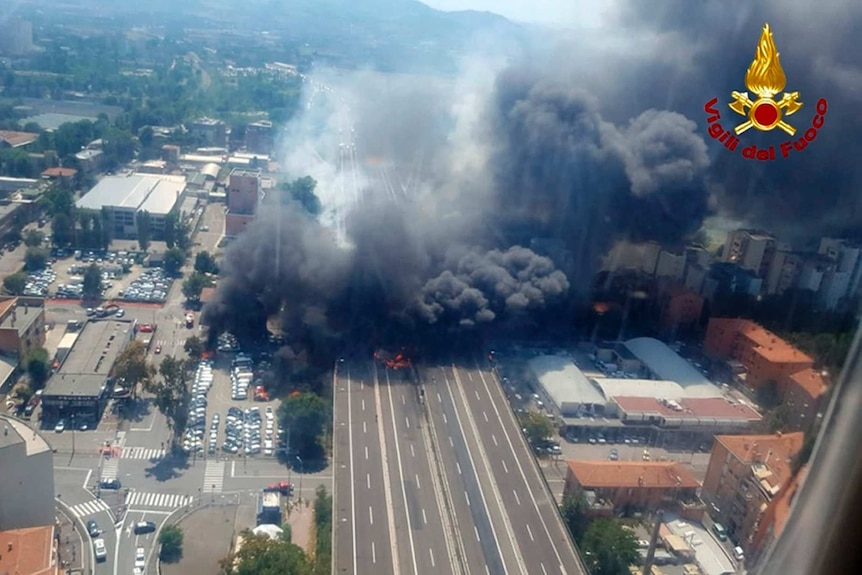 A photo from a helicopter gives a bird's eye view of black smoke and fire right across a highway after trucks collided.