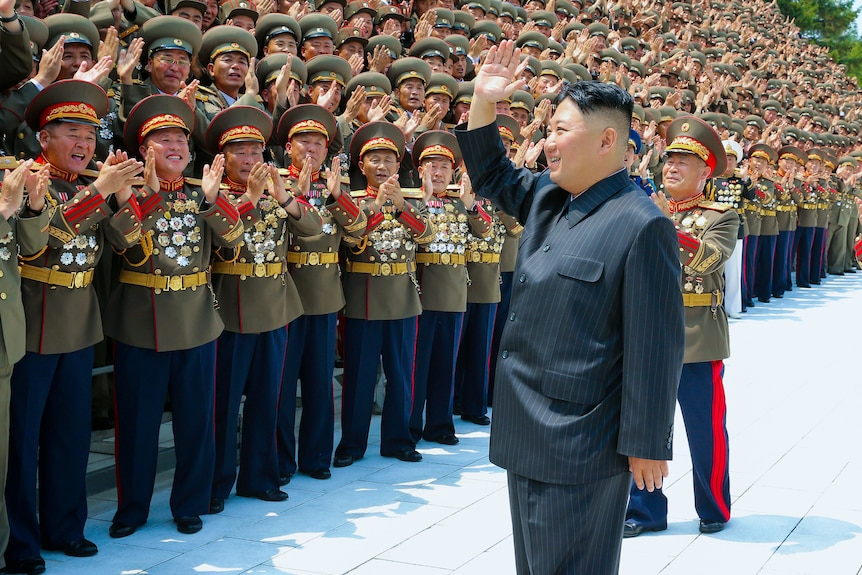 Kim Jong Un waves to a group of men in North Korean military dress uniforms