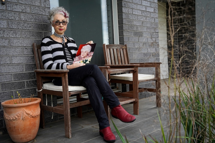 Peta Soorkia holds a photo of her mother on her front porch.