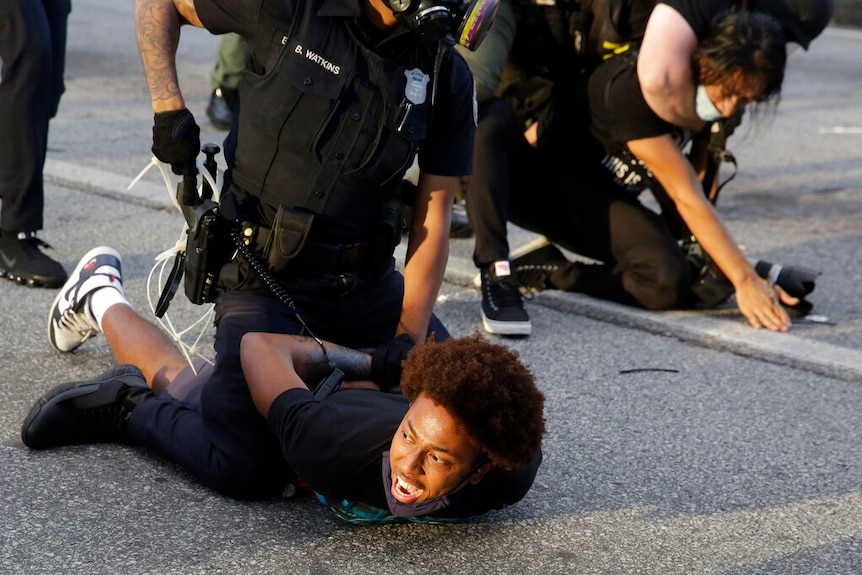 Demonstrators held on the ground by police.