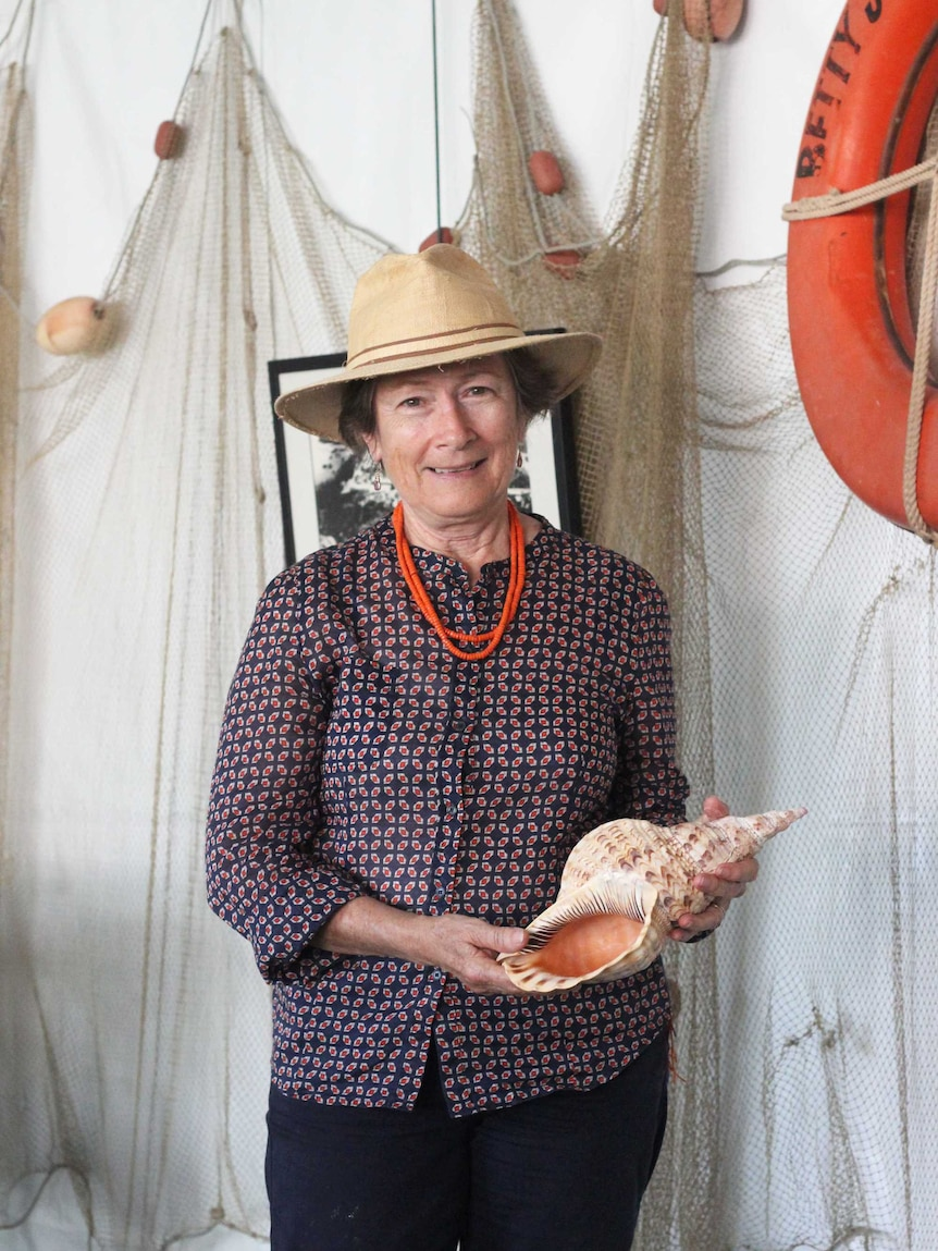 A woman holds a large shell.